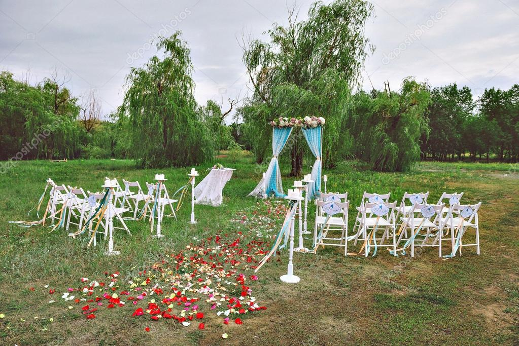 Beautiful wedding set up. wedding decor on the lawn, wedding arch, chairs with ribbons. turquoise, purple and white. The rose petals on the ground. Wedding ceremony