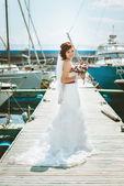 Fényképek Menyasszony fehér esküvői ruha a vonat, áll a pier kikötő