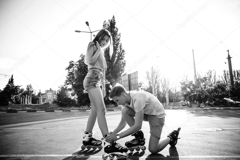 a couple roller skating at sunset black and white stock photo