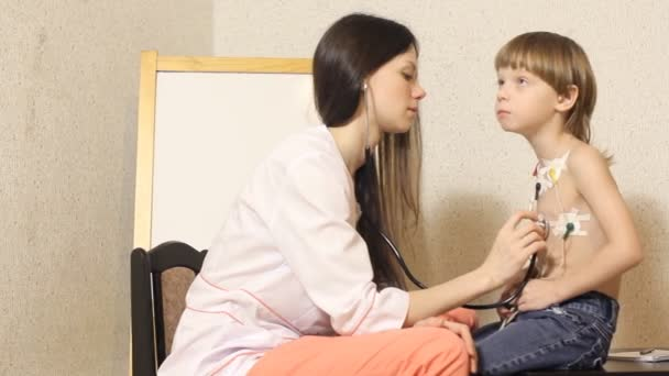 Kardiologin führt Empfang durch und untersucht den Jungen