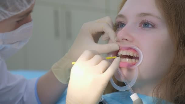 Orthodontist covering special gel on woman teeth in dentistry using brush.