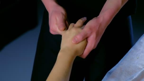 Massagist schrubbt Frau Hand und Finger natürliches Peeling im Wellness-Salon, Nahaufnahme.