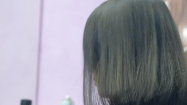 Bruneta žena na účes sestřih v salonu krásy, pohled zezadu.