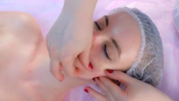 Kozmetológus orvos csinál myoplasticus arcmasszázs a nő a kozmetikai klinikán.