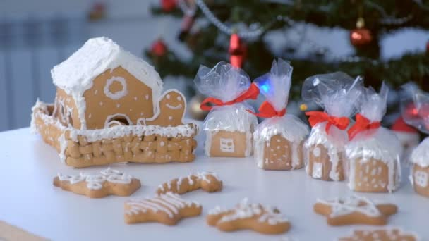 Mézeskalács házak és cookie-k csomagban karácsonyra fa háttér.