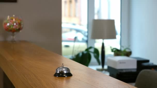 Reception at the hotel with a bell on a wooden table, closeup view.