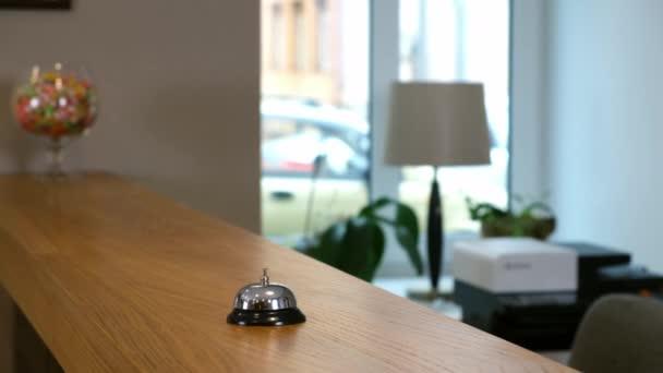 Recepce v hotelu se zvonkem na dřevěném stole, detailní pohled.