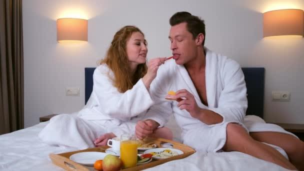 Mladý pár v županech se snídaní společně v posteli v hotelovém pokoji.