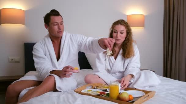Junges Paar in Bademänteln frühstückt gemeinsam im Hotelzimmer.