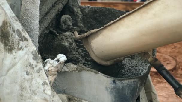 Beton wird von LKW-Mischer in Container auf Baustelle gegossen.