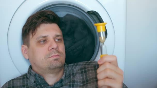 Mann mit Sandglas wartet auf Waschmaschine mit grauer Bettdecke darin.