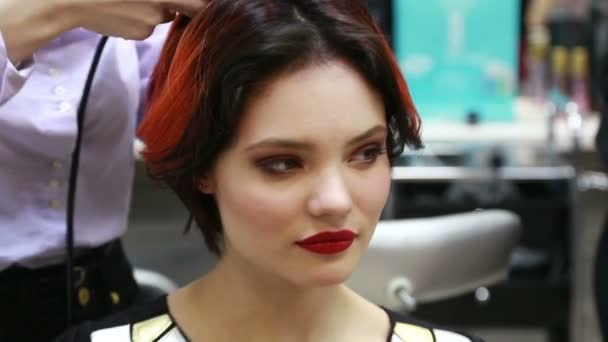 young sexy fashion model with red lipstick bright make up dancing laughing and joking while being made a hairstyle