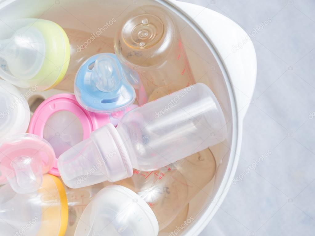 Nippel beißringe und milchflaschen in dampf sterilisator und