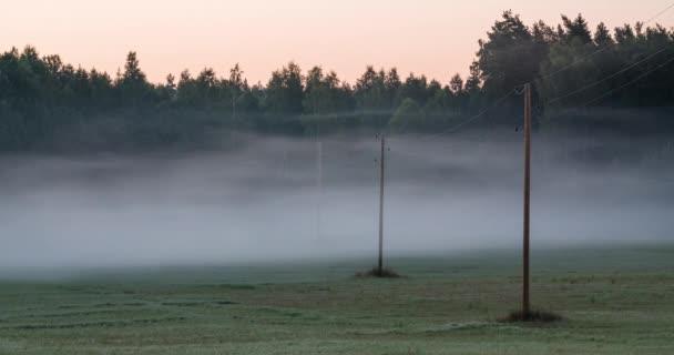 Časová prodleva ranní mlhy teče mezi elektrické vedení