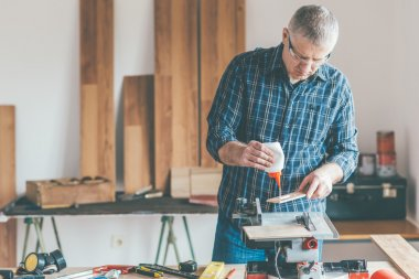 Carpenter applied glue on wooden board
