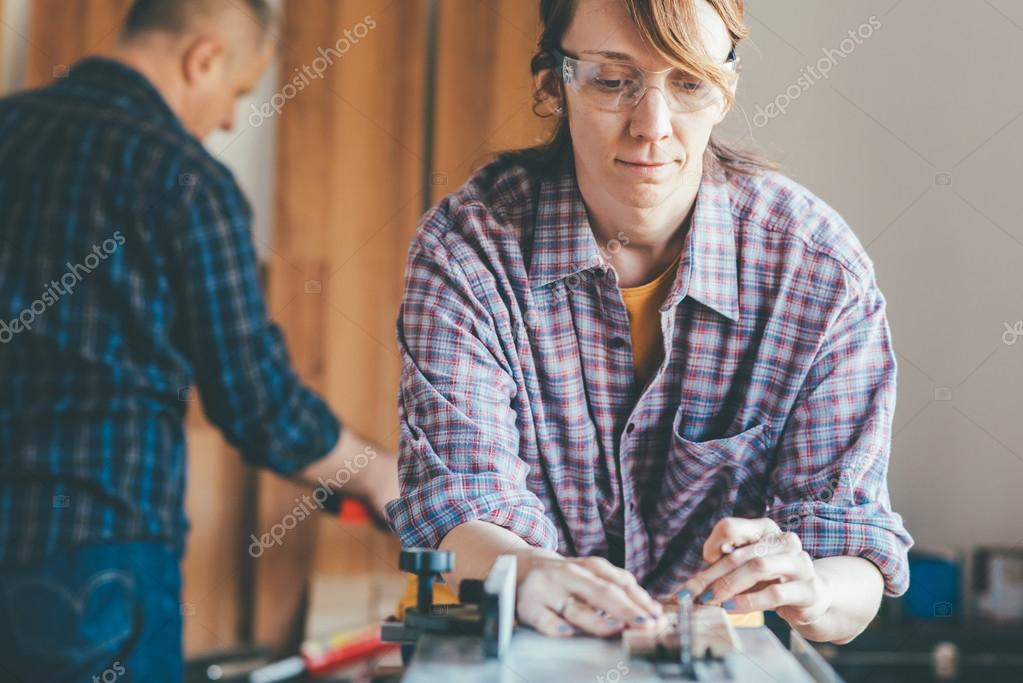 woman working at carpenter shop with teacher