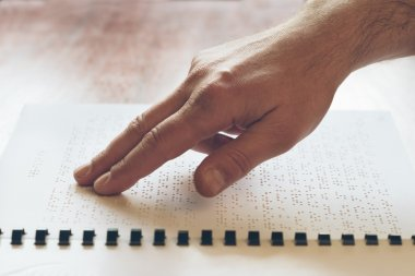 Visually impaired old person learning to reading by touch