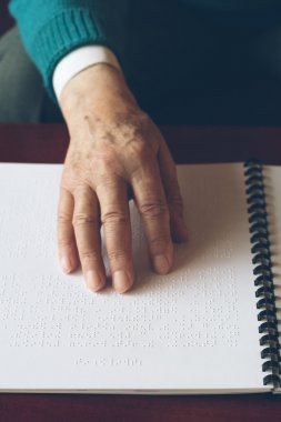 Visually impaired old person learning to reading by touch.