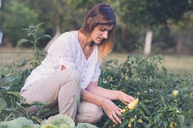 Young happy smiling woman working in organic field.