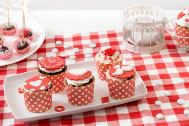 Cupcake in the red white wrapper, on the old wooden table...