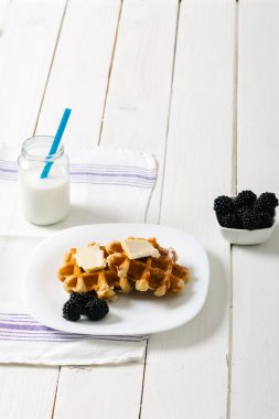 Homemade waffles with fruits on white vintage table