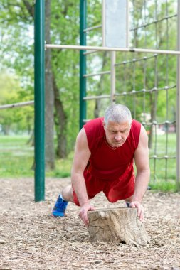 Senior Exercising In Sport Park