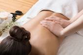Woman Receiving Back Massage in Spa Center.