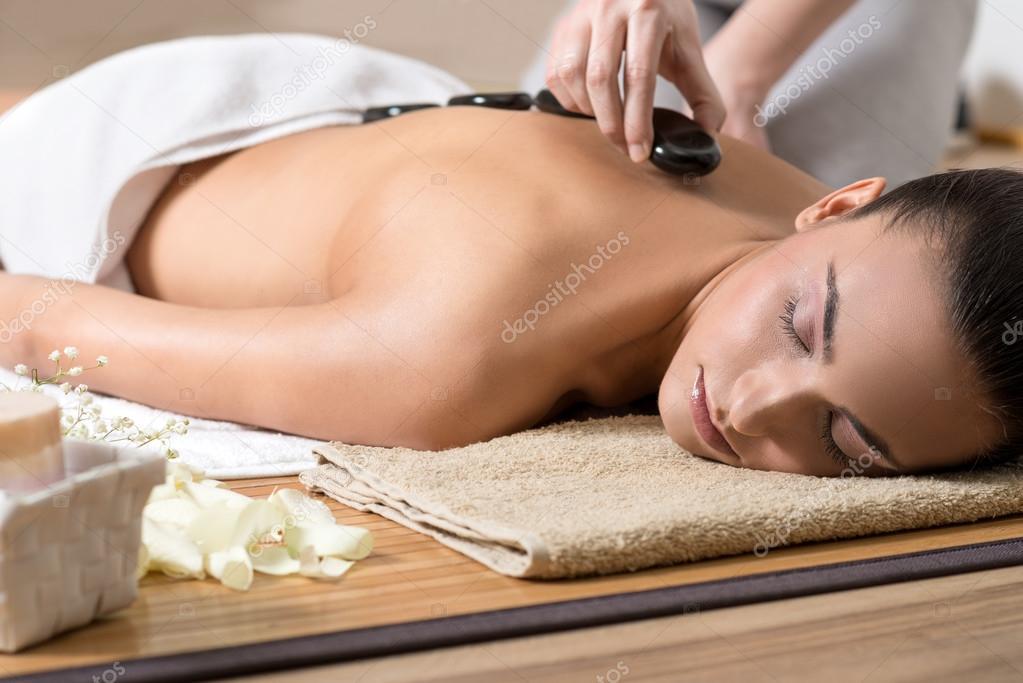 Woman Enjoying Hot Stone Ritual in Spa Center.