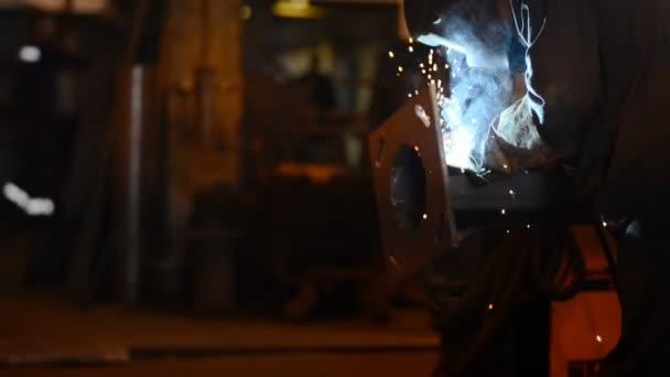 Svařovací inženýr svaru připojení základnu pipes.a spoustu jisker, kouř a světlo. výrobní zařízení