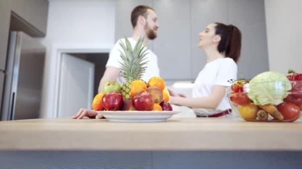 Mladý veselý pár v kuchyni diskutovat o ovoce a zelenině