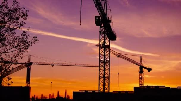Time lapse  cranes working in construction site at dusk, time lapse, 4k,tilt.Craner climbing