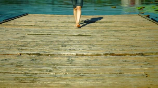Moje bosou nohou na dřevěných Pier.Girl v šortkách, chůzi na dřevěném molu