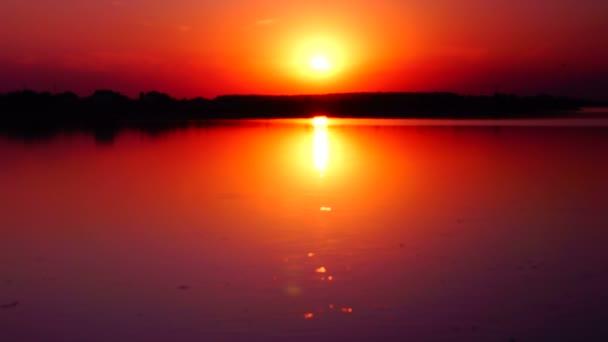 Beautiful sunset reflected in rippling lake
