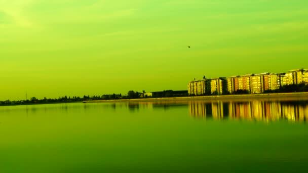 Městská krajina s jezerem při západu slunce a windows odráží v jezeře