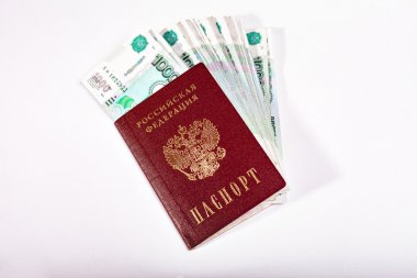 Money and Russian banknotes of denomination one and five thousand in the background. Passport of the Russian Federation