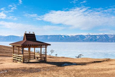 Traditional wooden gazebo on the shore of Lake Baikal