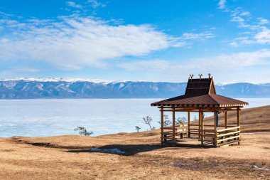 Winter Landscape on Olkhon island. Buryat region, Russia, Siberia. Traditional wooden gazebo in the Buryat-style on the shore of Lake Baikal in the winter mountains in the background.