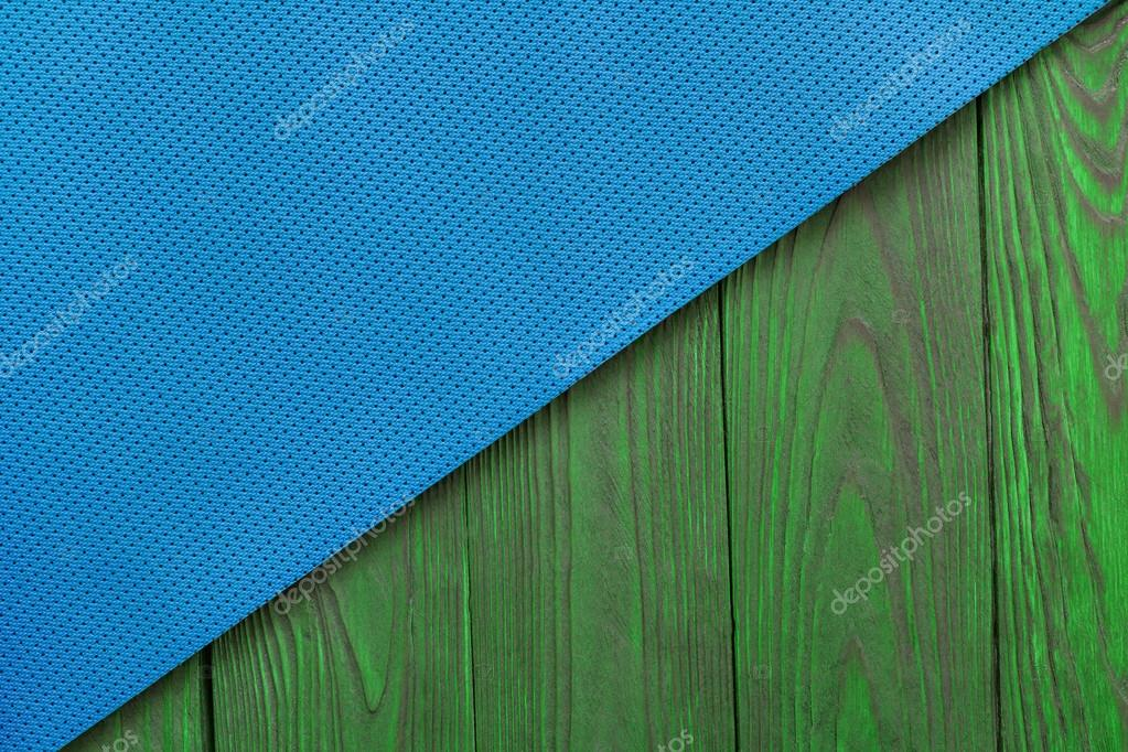 72d6734b1d17a Detail of perforated blue yoga mats on the wooden background. Texture yoga  mats and boards. Boards of green.