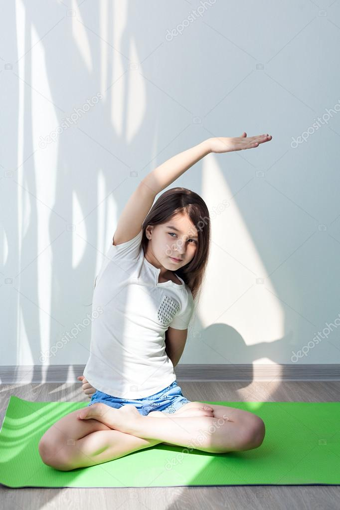 little girl doing gymnastics on a green yoga mat