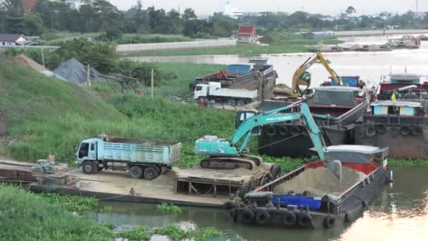 Backhoe scoops sand from ship to truck