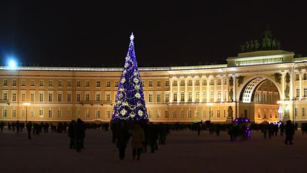 královský kočár projíždí a pěší turisté, vánoční stromeček třpytí na Dvortsovaya, palácové náměstí, Petrohrad