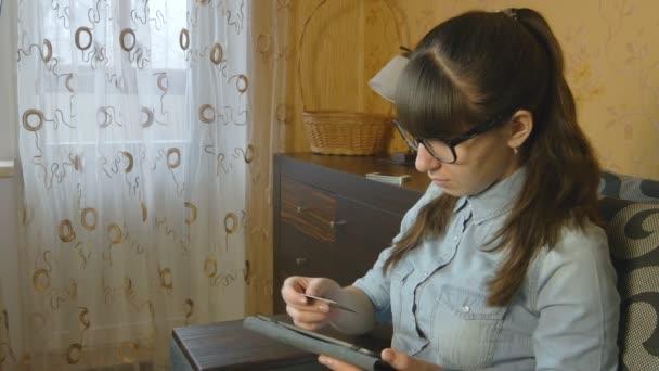 schöne Frau kauft online mit Kreditkarte und Tablet zu Hause ein