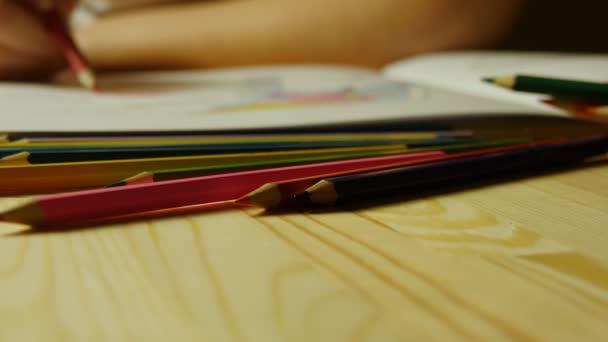 Barevné tužky na pozadí ženské ruce kreslí dospělých omalovánky