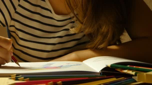 Atraktivní dívku v brýlích kreslí omalovánky. Zblízka