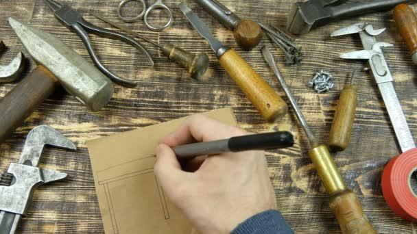 Der Mann zeichnet einen Entwurf. gibt Dimensionen an. Oldtimer-Werkzeuge im Hintergrund