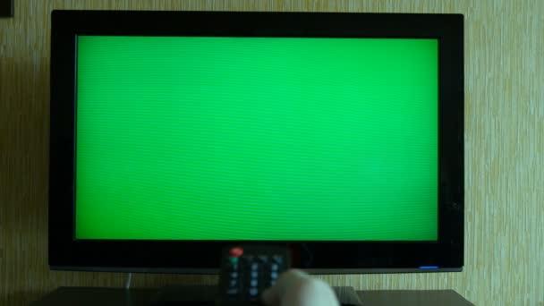 Mužské ruky s Tv dálkové přepínání kanálů na zelenou obrazovku Tv úhlu pohledu
