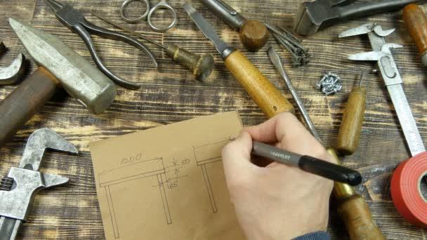 Člověk nakreslí návrhu. Udává rozměry. Vintage nástroje na pozadí