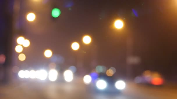 Auta projíždějící červeným světelním signálem. Zaostření na pozadí s rozmazlané světlíky a poháry aut a světla