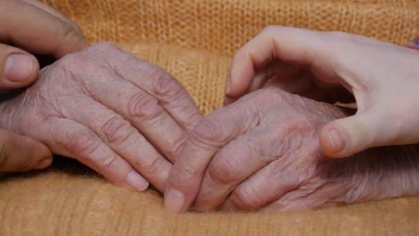 Mladý samec a samice ruce uklidňující staré pár rukou venkovní.
