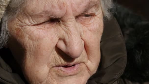 Portrait of old talking woman . Serious grandmother sitting outdoor and speaking. Close-up